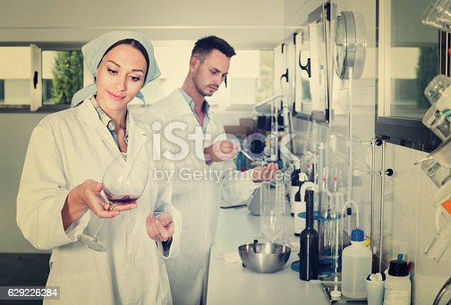istock Two researchers in white coat checking wine acidity in laborator 629226284