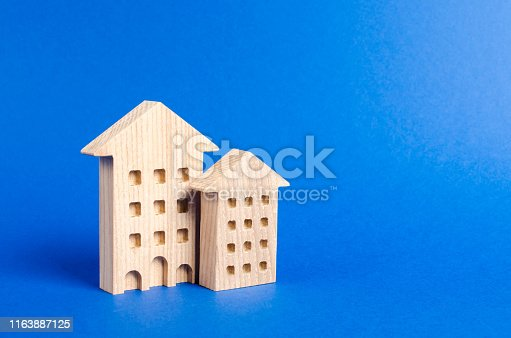 istock Two residential buildings stands on a blue background. The concept of buying and selling real estate, renting. Search for a Apartment house. Affordable housing, credit and loans. place for text 1163887125