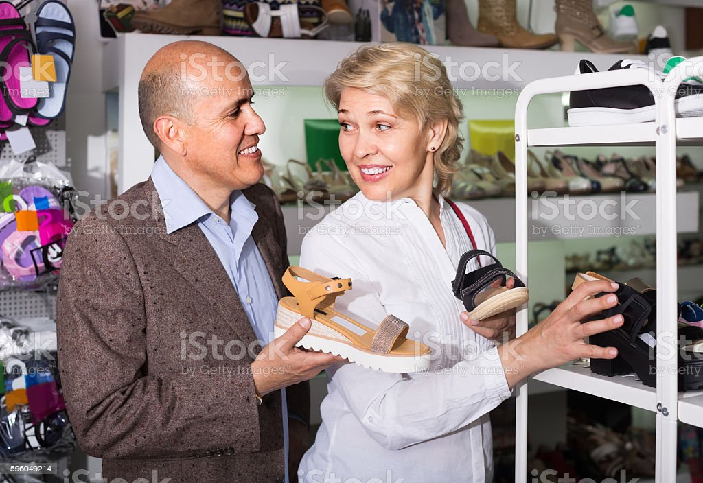 Two retirees together choosing pair of shoes in fashion store royalty-free stock photo