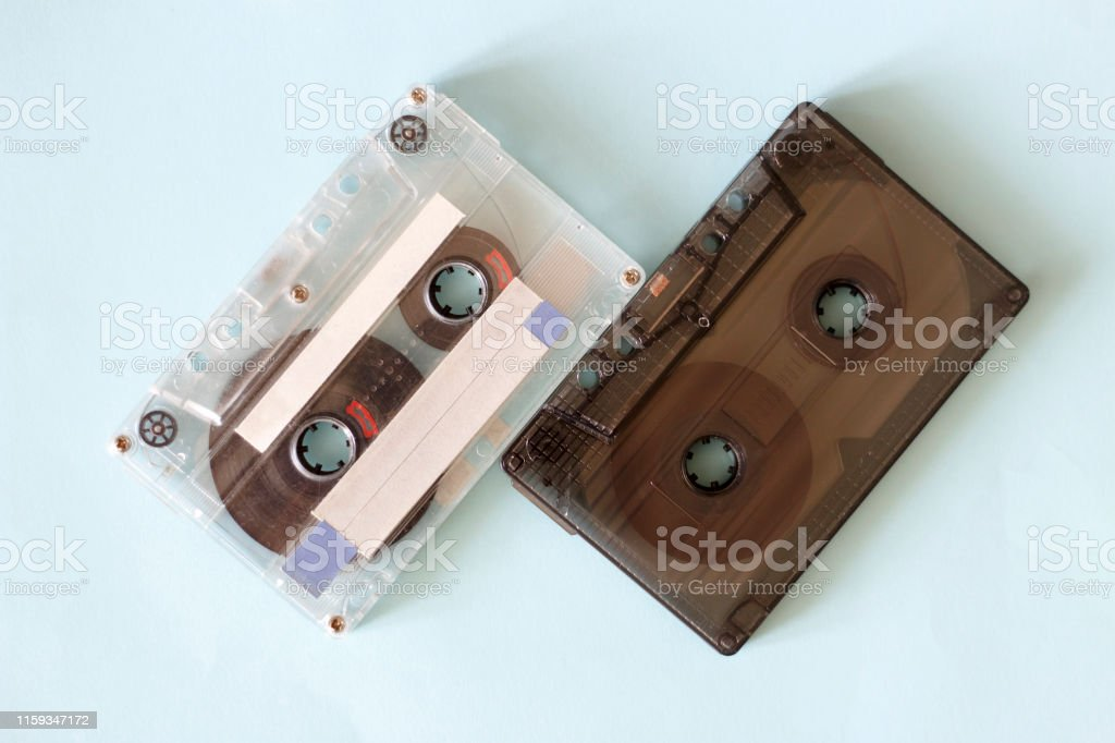 Two retro audio cassettes, close up on a blue background, vintage...