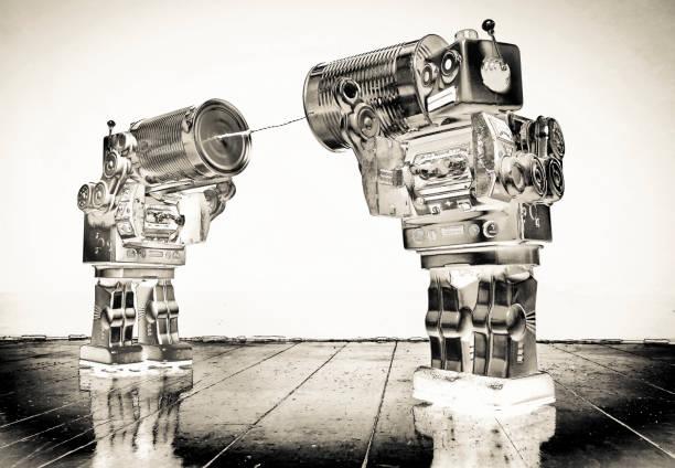 zwei retro-roboter spielzeug reden auf blechdose handys solarisierte monochrom - converse taylor stock-fotos und bilder
