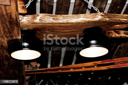 Two retro style lamps on a wooden ceiling close up
