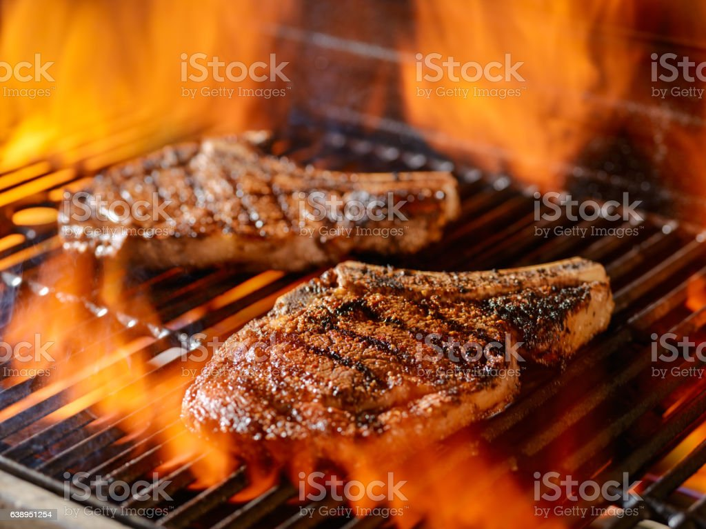 two rib-eye steaks grilling on the open flame stock photo