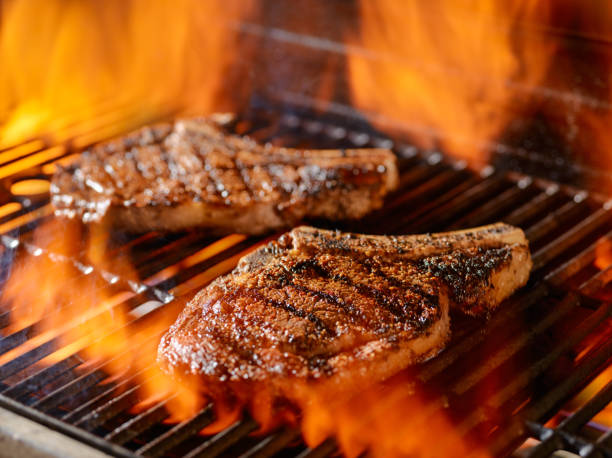 two rib-eye steaks grilling on the open flame - ribeye biefstuk stockfoto's en -beelden
