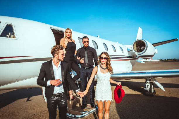 Two rich and famous couples exiting a parked private jet parked on an airport tarmac Two rich and famous couples exiting a private airplane parked on an airport taxiway. status symbol stock pictures, royalty-free photos & images