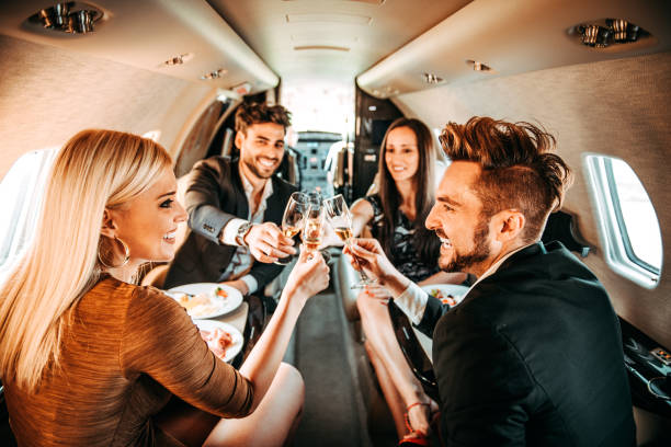 Two rich couples putting their glasses together in a celebratory toast while traveling on a private airplane Two upper class couples putting their glasses together in a celebratory toast while traveling aboard a private jet. Plates of food are on the tables. status symbol stock pictures, royalty-free photos & images
