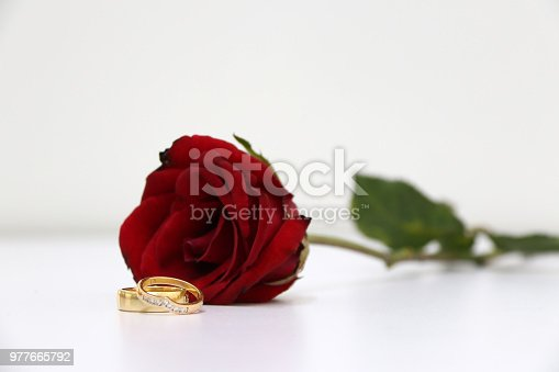 867916232 istock photo Two ring and red color of rose with green leaf on the white floor. 977665792