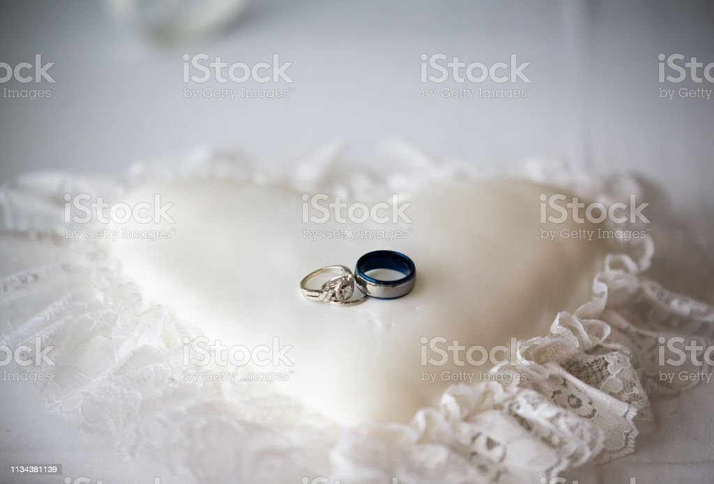 Two wedding rings placed on a heart pillow