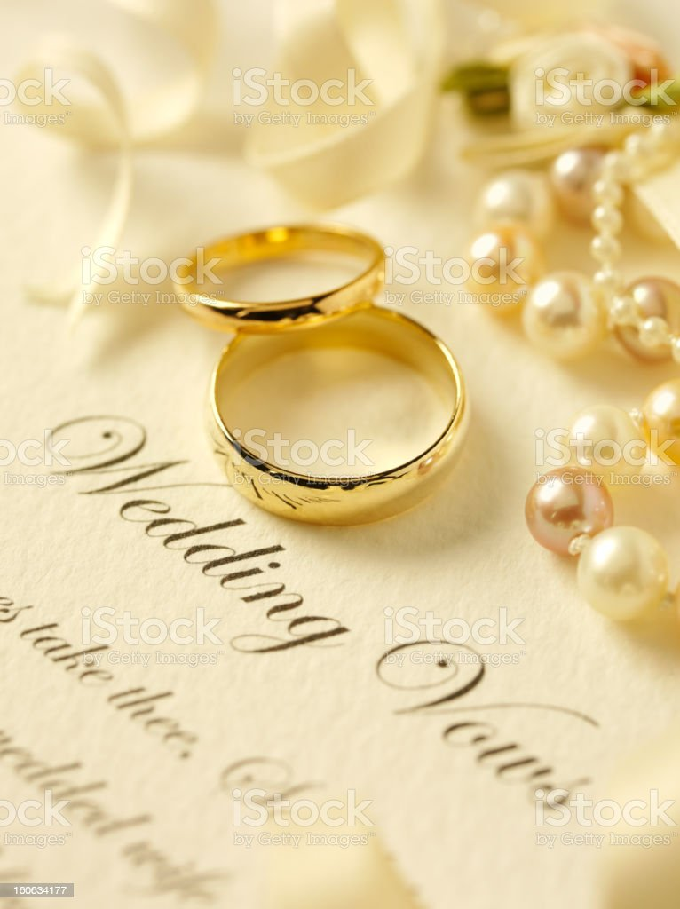 Two gold wedding rings with pearls on wedding vows.