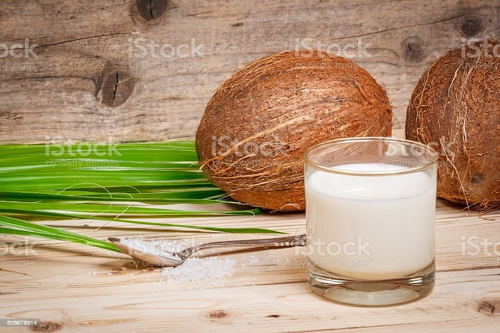 Two ripe coconut from leaf palm at wooden - foto de acervo