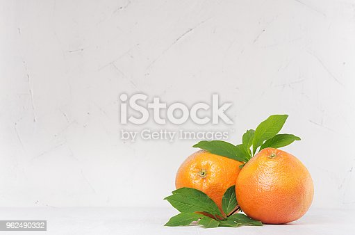 istock Two ripe fresh grapefruits with green leaf on light white kitchen interior. Healthy food background with copy space. 962490332