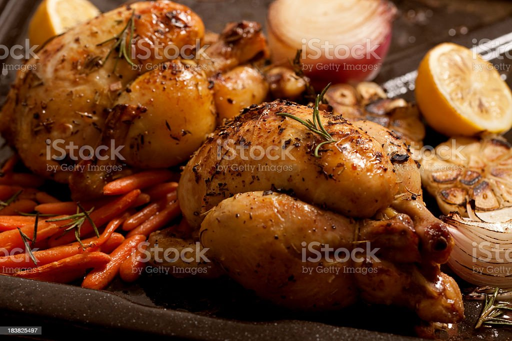 Two roasted chicken with baby carrots, onion and lime royalty-free stock photo