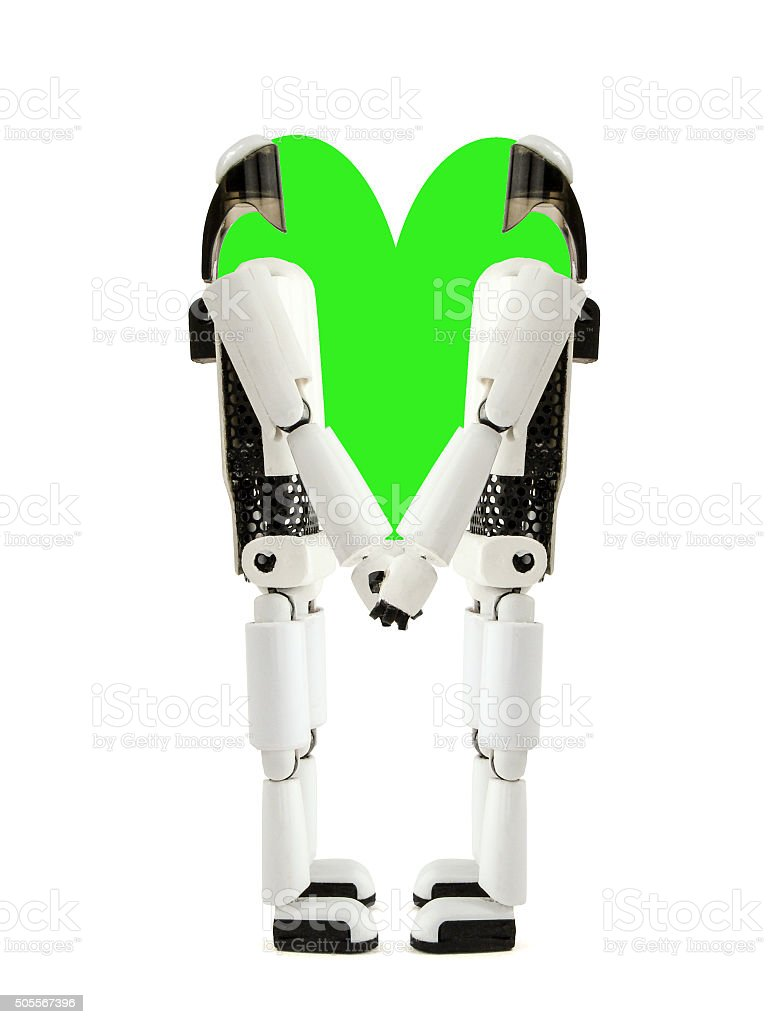two robots hold hands with green heart stock photo