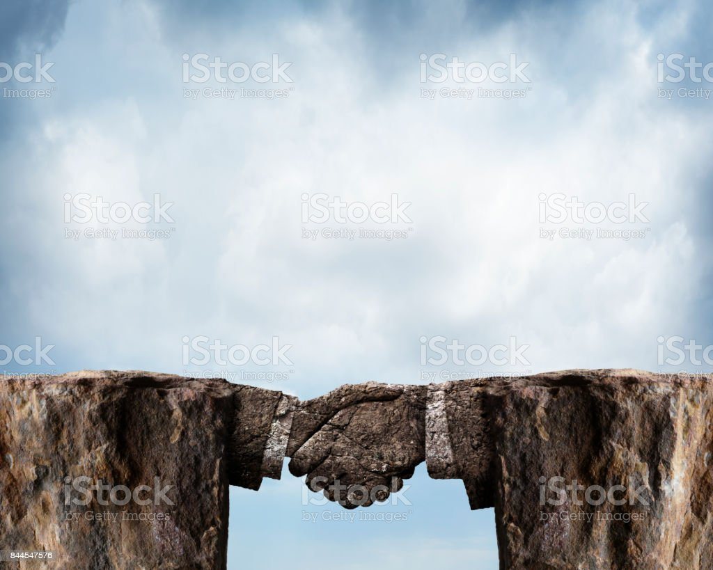 Two Rocky Cliffs Joined By Handshake Carved From Stone stock photo
