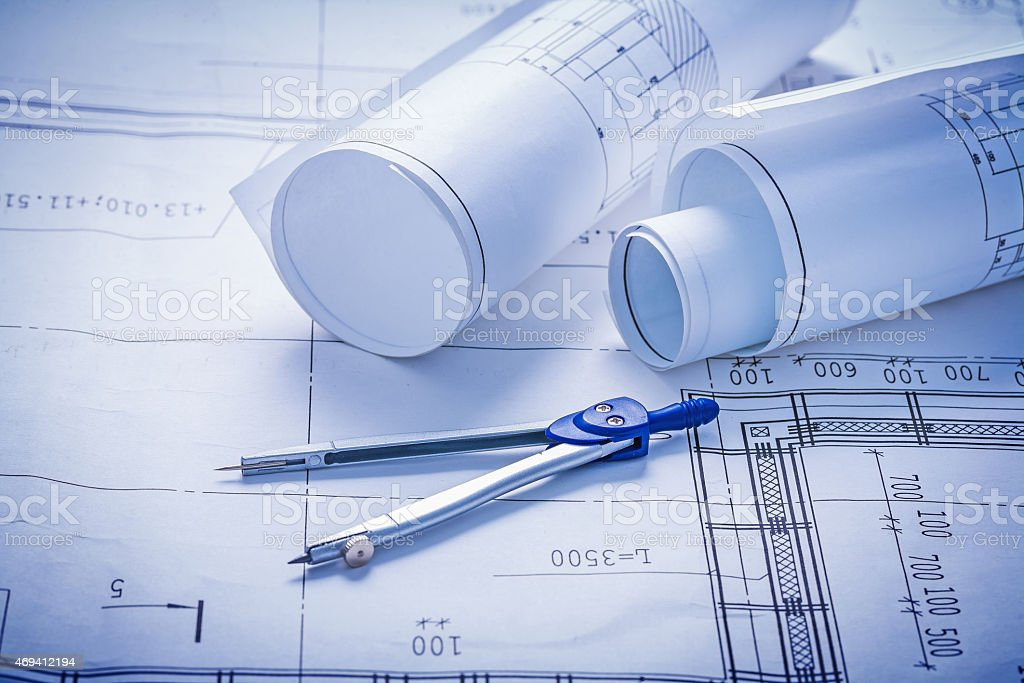 two rolled up blueprints and compass construction concept stock photo