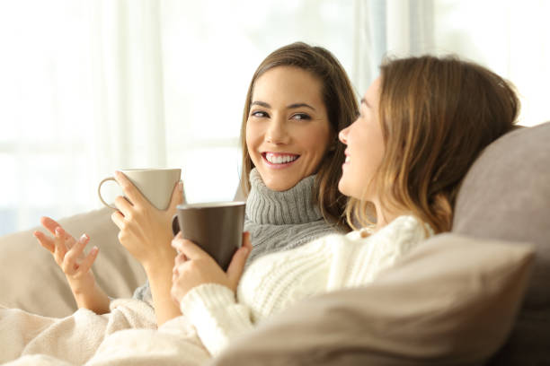 Two roommates talking on couch in winter stock photo