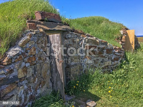two root cellars in grassy hillside on Fogo Island, Newfoundland