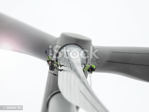 Two rope access technicians doing wind turbine blade inspection and waving with sun behind