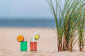 Two rose and green lemonade glasses on sand between marram grass at beach
