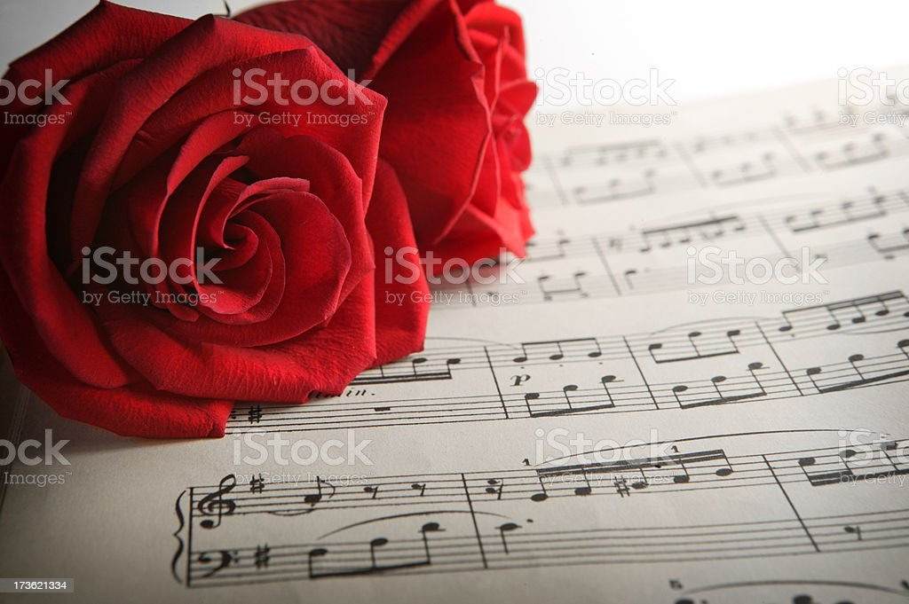 Two roses lie on top of a piece of sheet music royalty-free stock photo