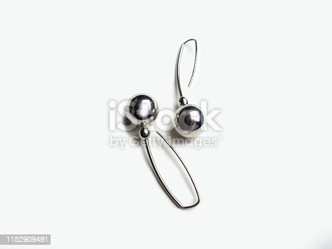 Two round white gold earrings on white background