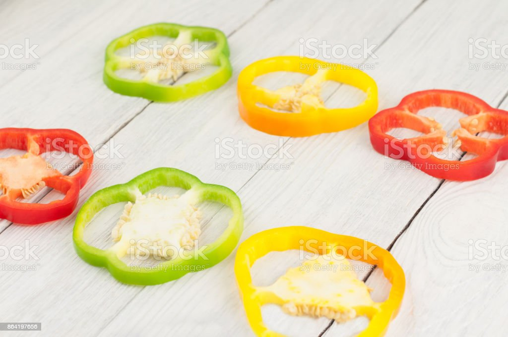 Two row of slices of colored red and green and yellow fresh ripe raw pepper on old rural white wooden planks royalty-free stock photo