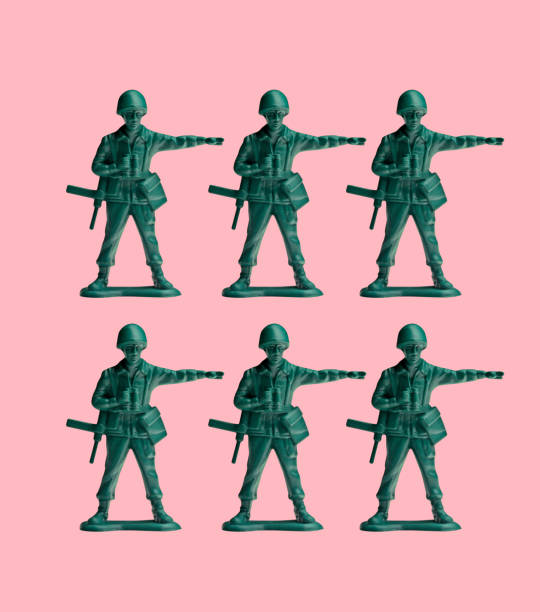 Two Rows Of Green Toy Army Men On A Pink Background stock photo