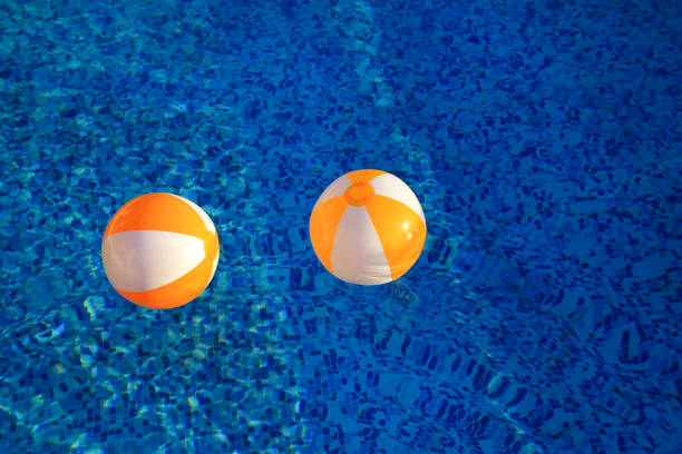 Two rubber air yellow white inflatable balls and toy for swimming pool in transparent blue water. Multi-colored beach balls floating on water in blue swimming pool for concept relax holiday travel. stock photo