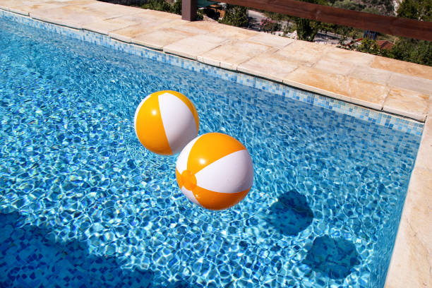 Duas esferas e brinquedo infláveis brancos amarelos do ar de borracha para a piscina na água azul transparente. Esferas multi-colored da praia que flutuam na água na piscina azul para o conceito relaxa o curso do feriado. - foto de acervo