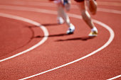 istock Two runners on a track in running shoes racing 183770092