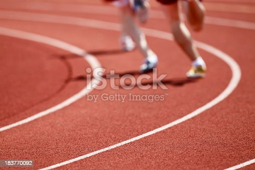 A group of runners rounds a curve on an all weather running track.  Shot with a 400mm lens at 2.8 to produce a very shallow depth of field.  The rough surface of the track combined with the shallow depth of field make a great pattern.