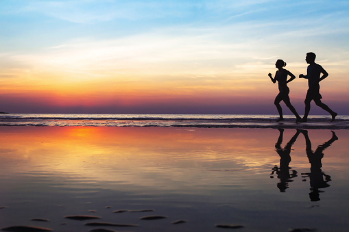 two runners on the beach, silhouette