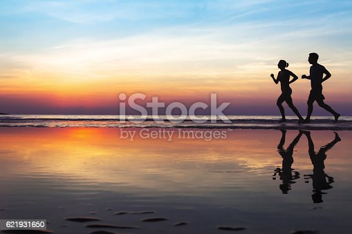 istock two runners on the beach, silhouette 621931650