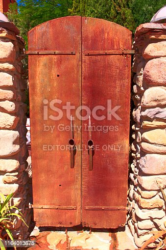 Two rusty metal doors with pick-axe heads for handles leading to the Courtyard Restaurant on Brewery Ave in downtown Bisbee, AZ