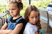 istock Two sad depressed girl punished standing together turned back on the back 1160000671