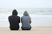 Back view of two sad teenagers sitting on the sand of the beach and looking at horizon in a bad weather day