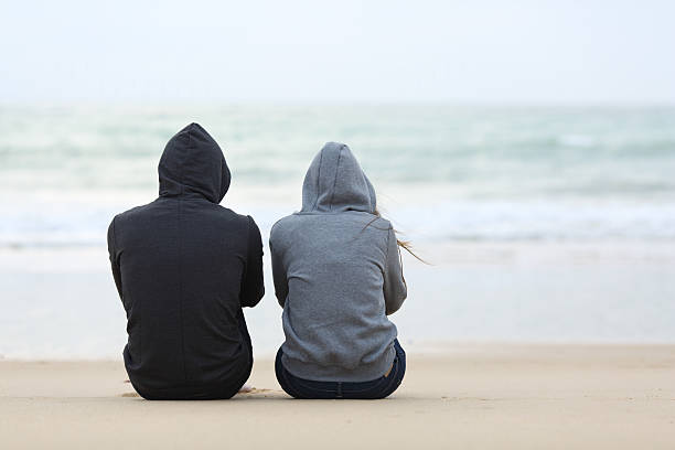 two sad teenagers sitting on the beach - grief stock photos and pictures