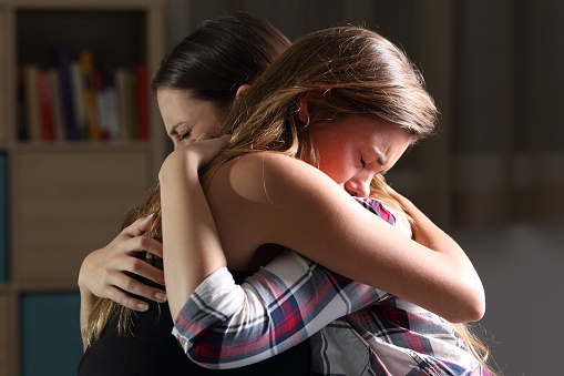 Side view of two sad good friends embracing in a bedroom in a house interior with a dark light in the background