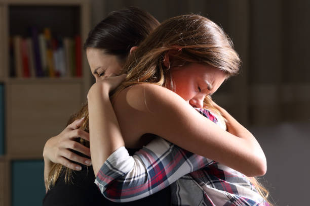 Two sad teens embracing at bedroom Side view of two sad good friends embracing in a bedroom in a house interior with a dark light in the background crying stock pictures, royalty-free photos & images