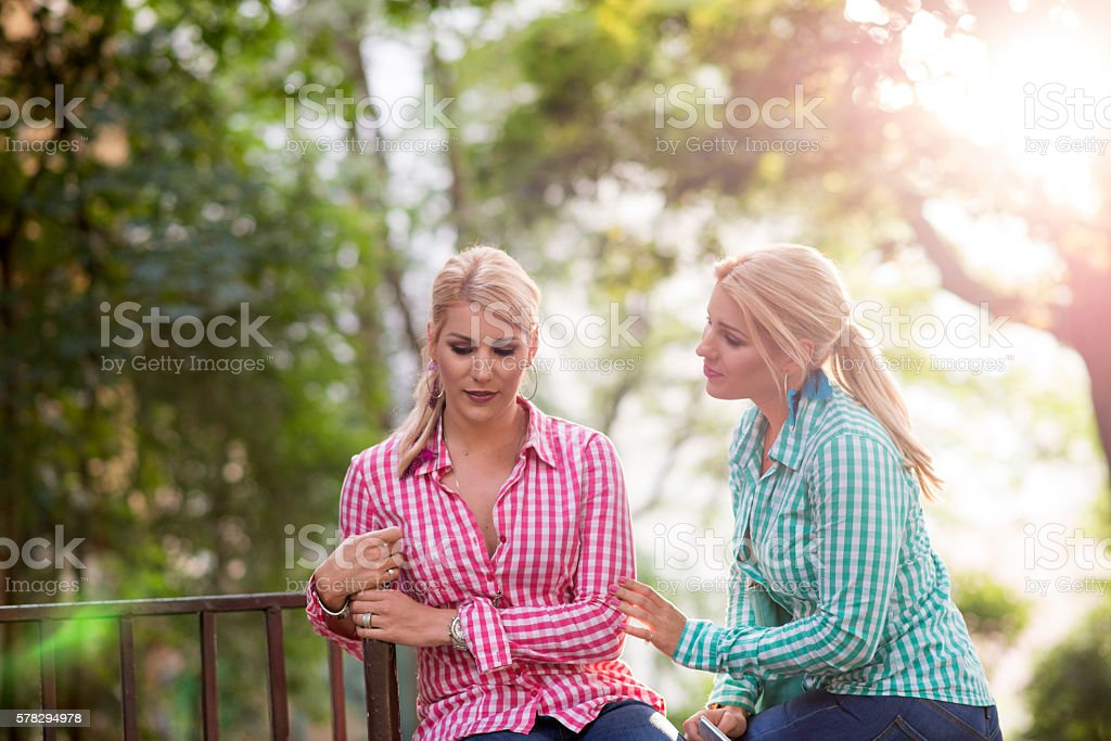 Two sad young beautiful girls portrait outdoors stock photo