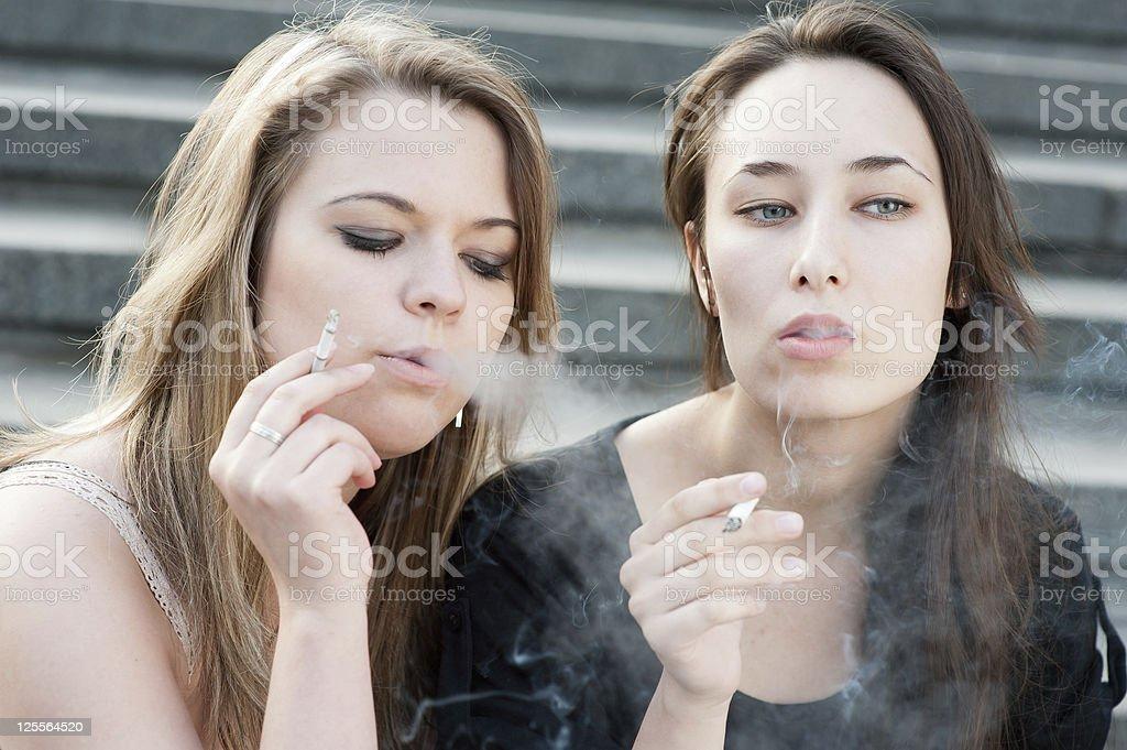 Two sad young girls smoke stock photo