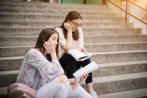 zwei leider hohe schulmädchen sitzen auf treppe außerhalb der schule und hausaufgaben machen. - kindergeldantrag stock-fotos und bilder