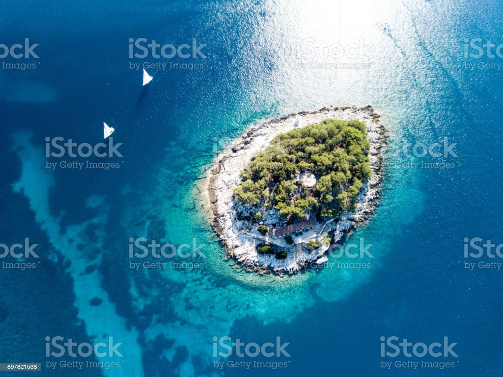 two sailboats and an island stock photo