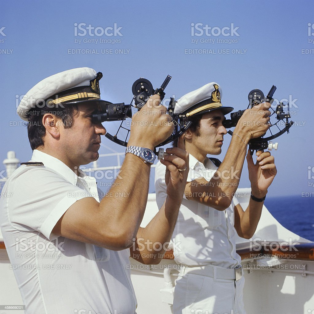 Two sailors calculating the route with the sextant stock photo