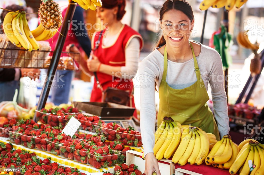 Two saleswoman on fruit market selecting fresh fruit and preparing for working day. stock photo