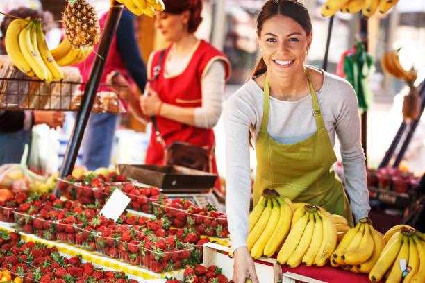 과일 두 판매원 시장 신선한 과일을 선택 하 고 작업 일에 대 한 준비. - 바자 뉴스 사진 이미지