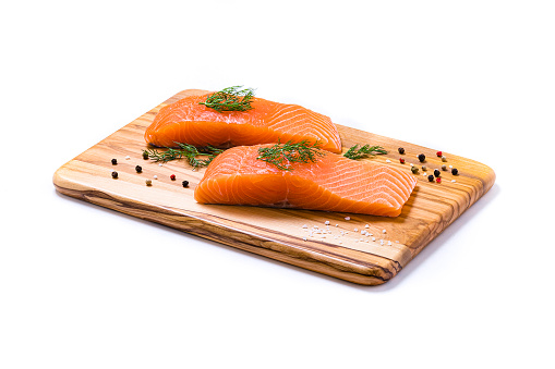 High angle view close-up of two salmon fillets on a wooden cutting board surrounded by some dill leaves and pepper. The cutting board is isolated on white background. Studio shot taken with Canon EOS 6D Mark II and Canon EF 100 mm f/ 2.8