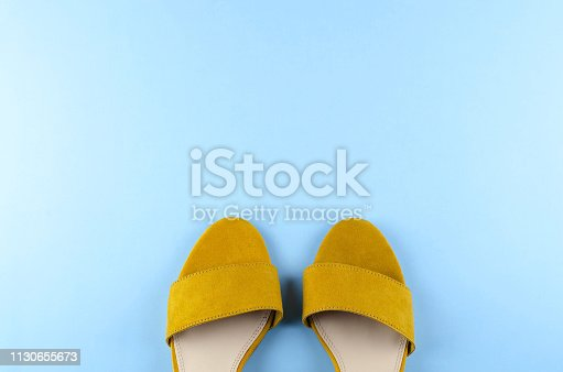 istock Two sandals mustard color blue background. 1130655673