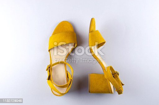istock Two sandals mustard color gray background. 1132729046