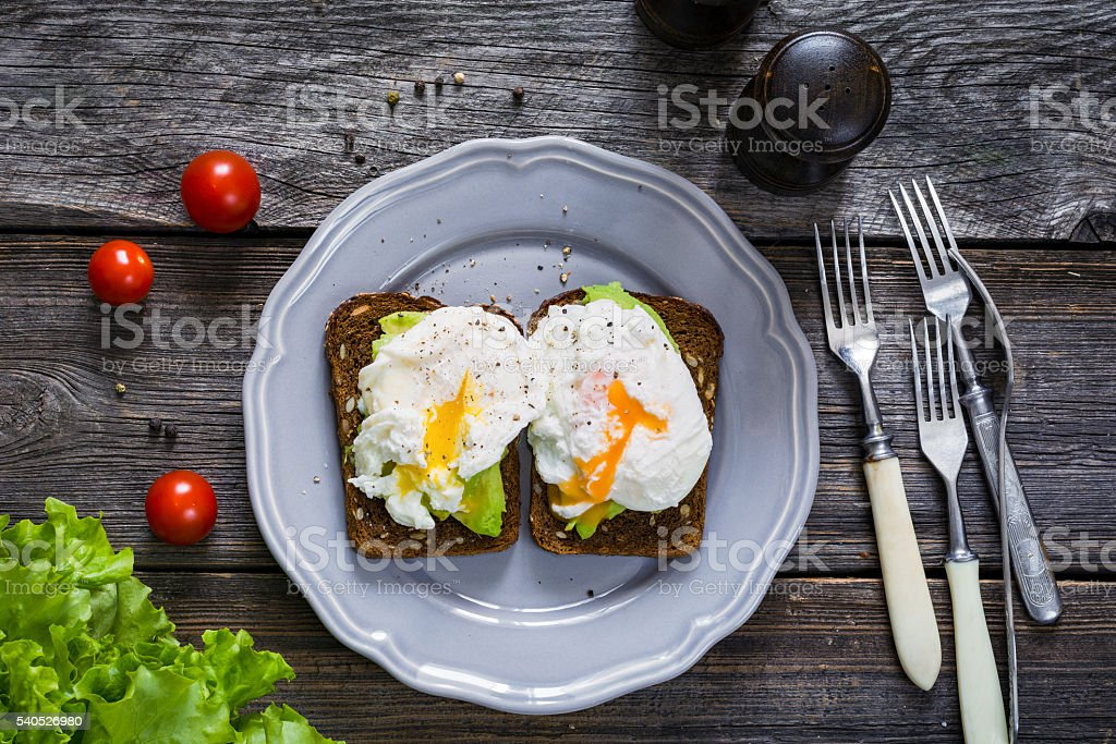 Two sandwiches with avocado and egg on a plate stock photo